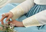 Closeup of hands of woman sitting and wearing a custom womens bridal hanbok with white top and blue skirt