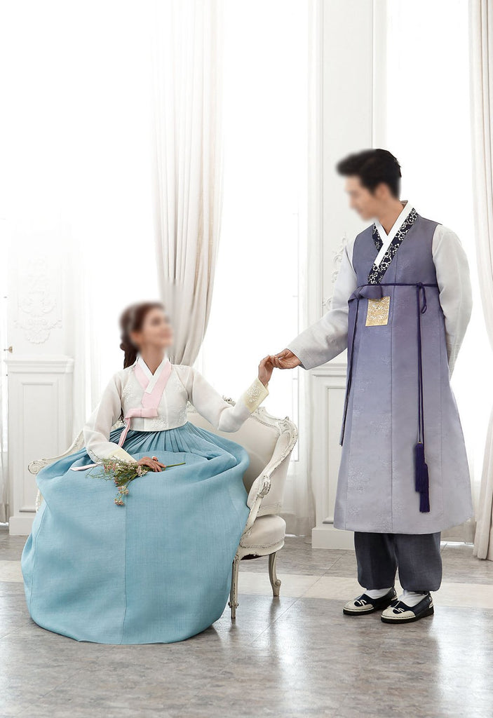 Woman talking to man and wearing a custom womens bridal hanbok with white top and blue skirt