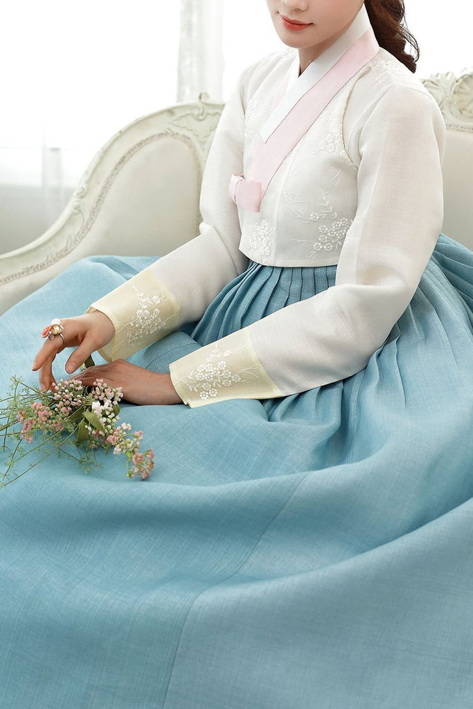 Woman sitting and wearing a custom womens bridal hanbok with white top and blue skirt