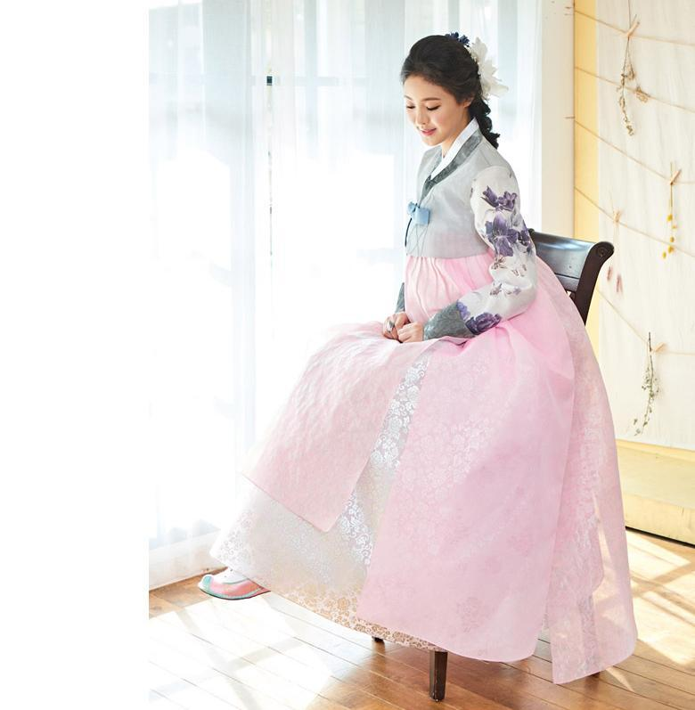 Woman sitting on a high chair and wearing a custom womens bridal hanbok with pastel and pink style