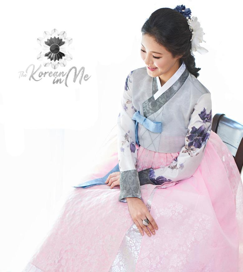 Woman sitting and wearing a custom womens bridal hanbok with pastel and pink style