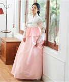 Woman standing by window and wearing a custom womens bridal hanbok in pink