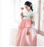Woman holding a flower and wearing a custom womens bridal hanbok in pink