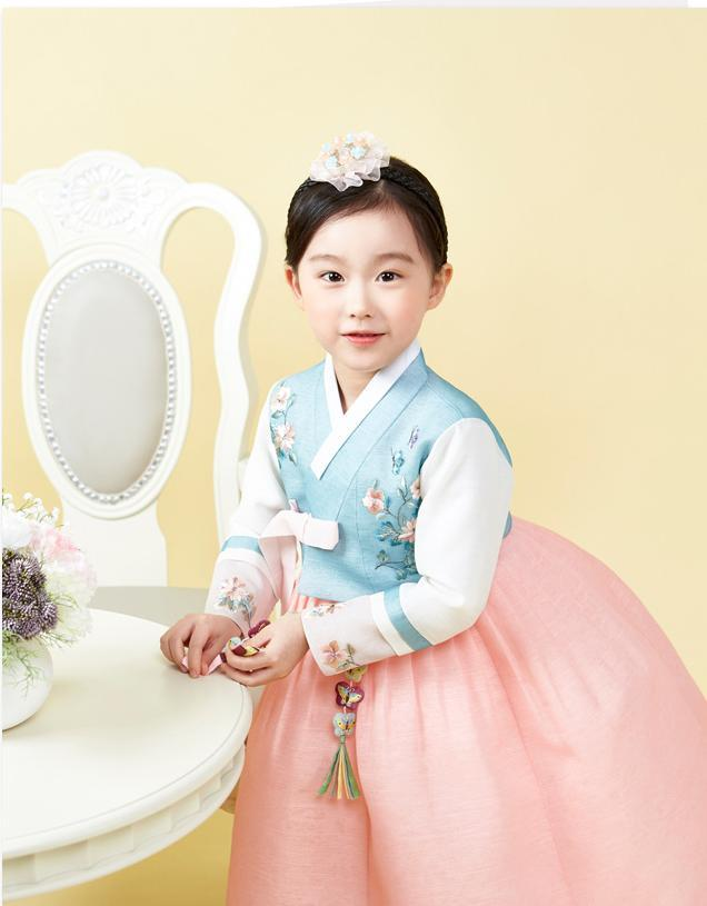 Young girl standing near table and wearing a girls korean hanbok with blue floral top and pink skirt