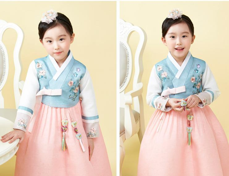 Young girl posing and wearing a girls korean hanbok with blue floral top and pink skirt