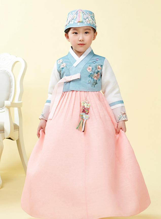 Young girl wearing a girls korean hanbok with blue floral top and pink skirt