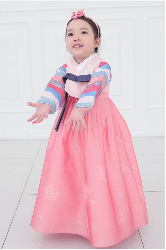 Young girl holding arms out and wearing a girls korean hanbok with pink top and skirt