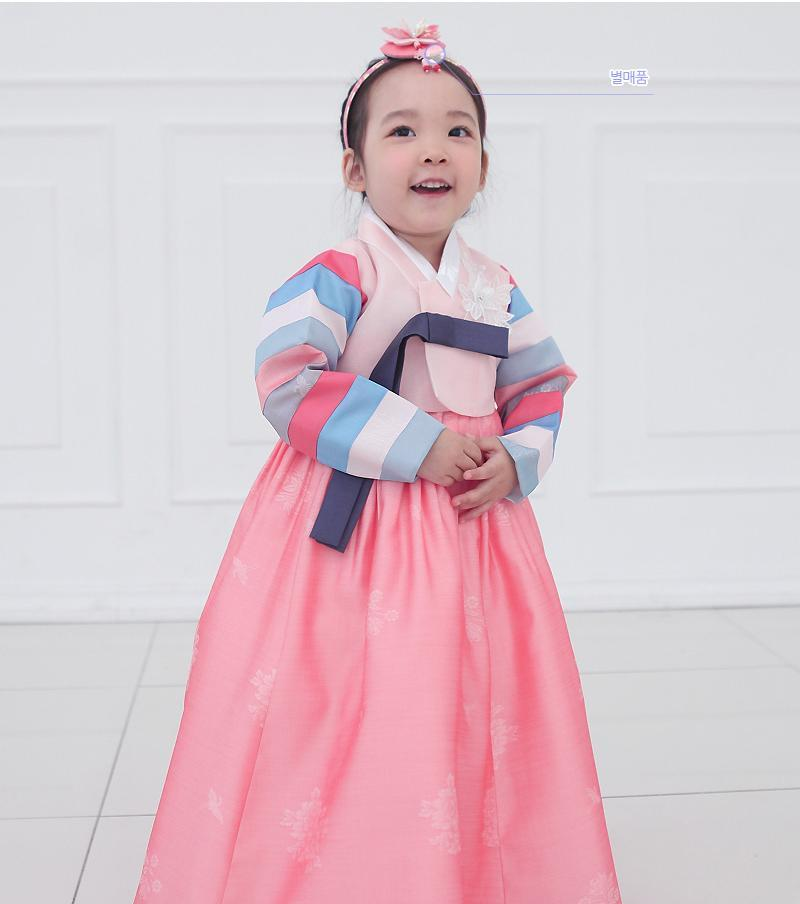 Young girl clasping hands and wearing a girls korean hanbok with pink top and skirt