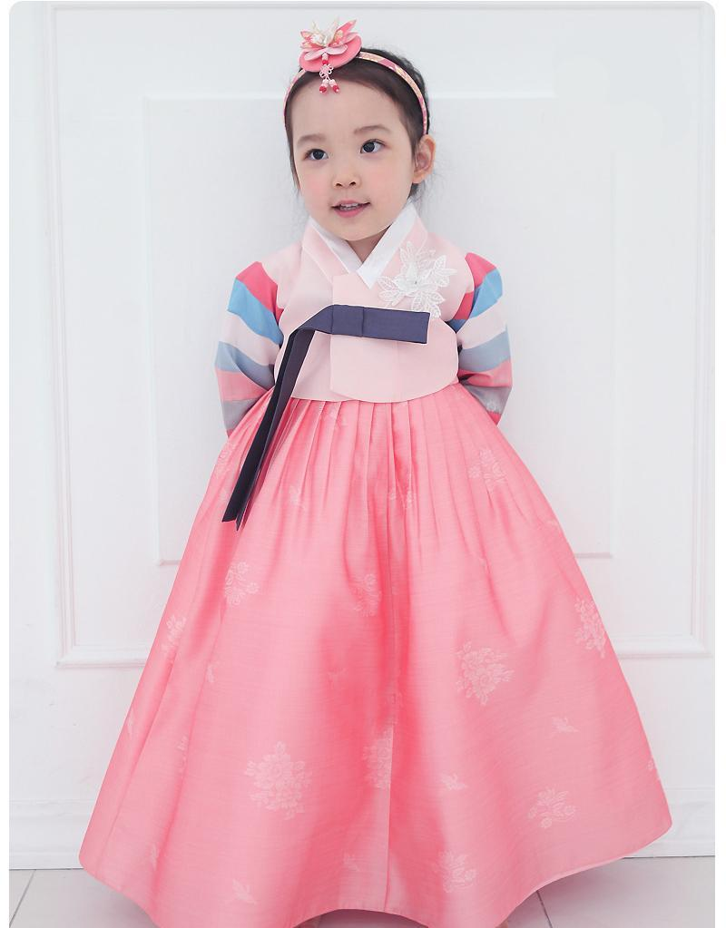 Young girl with hands behind her back and wearing a girls korean hanbok with pink top and skirt