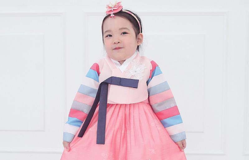 Young girl funny face and wearing a girls korean hanbok with pink top and skirt