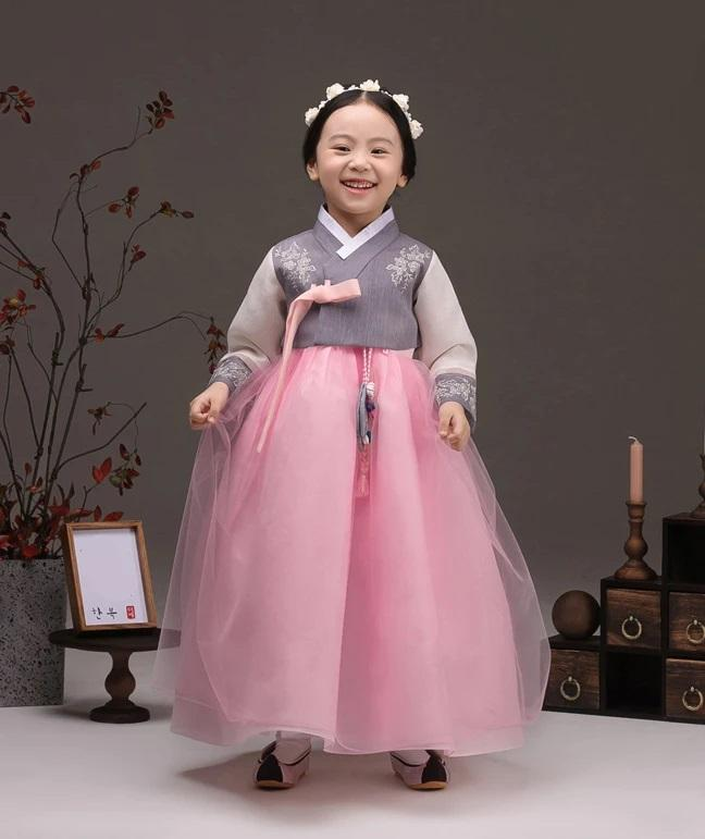 Young girl smiling and wearing a girls korean hanbok with lavender top and pink skirt
