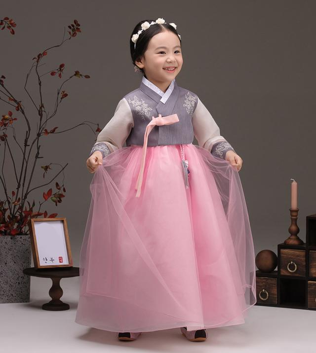 Young girl holding her skirt and wearing a girls korean hanbok with lavender top and pink skirt