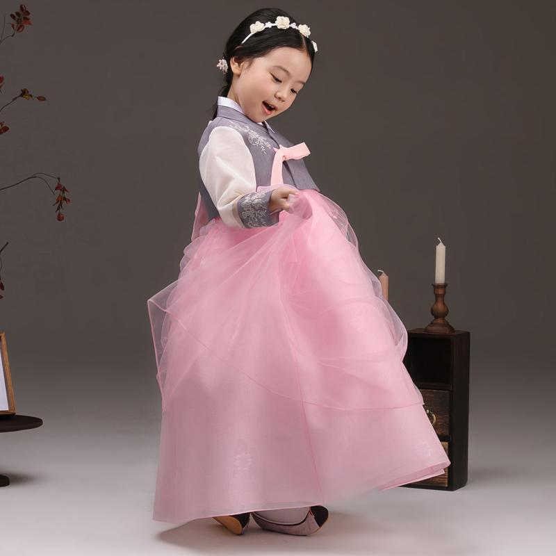 Young girl examining her skirt while wearing a girls korean hanbok with lavender top and pink skirt