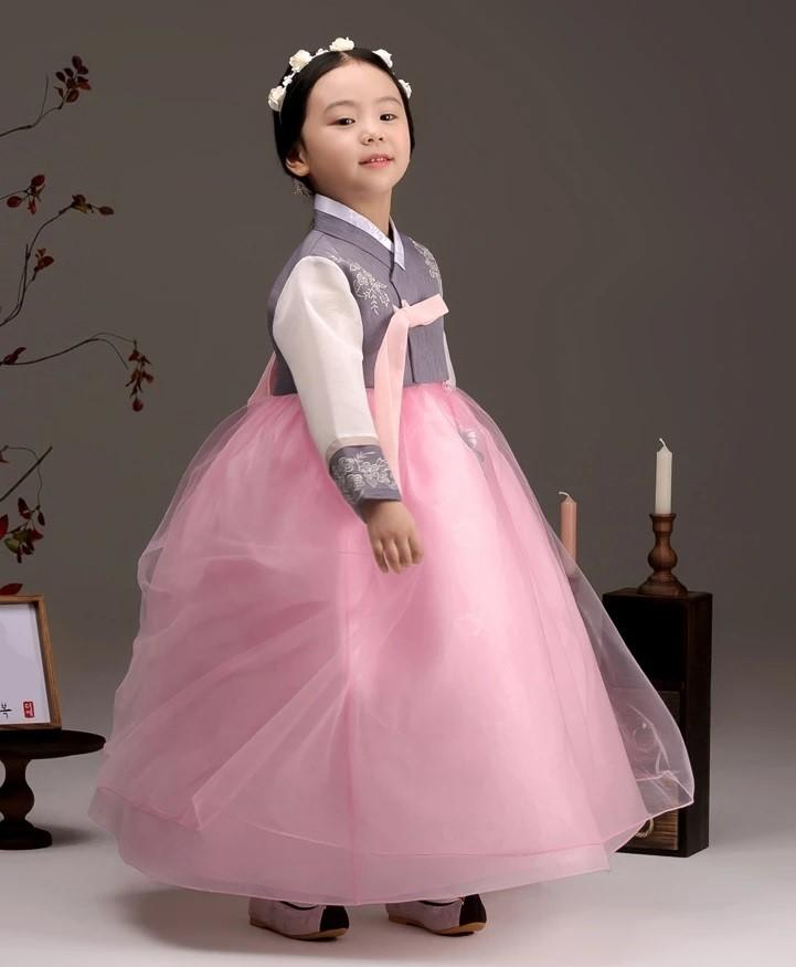 Young girl wearing a girls korean hanbok with lavender top and pink skirt