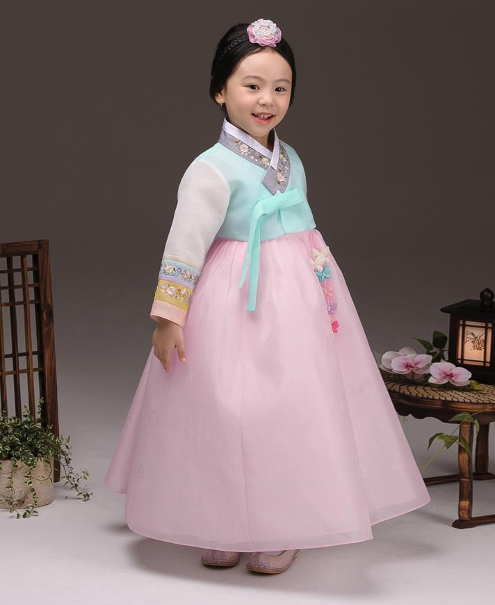 Young girl wearing a girls korean hanbok with pastel blue top and pink skirt