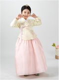 Young girl pointing at cheeks and wearing a girls korean hanbok with pastel yellow top and pink skirt