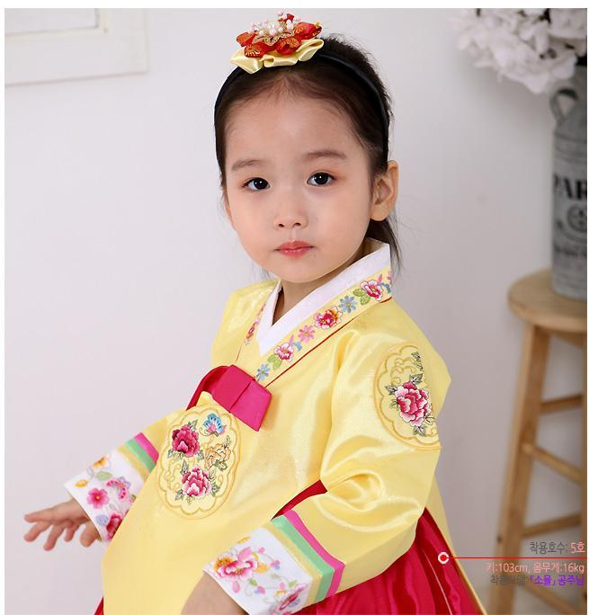 Young girl wearing a girls korean hanbok with yellow top and bright red skirt