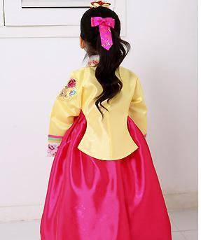 Back view of young girl wearing a girls korean hanbok with yellow top and bright red skirt