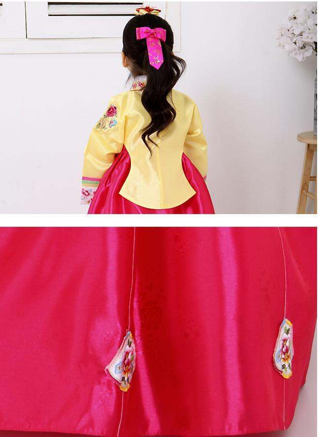 Closeup of skirt of a girls korean hanbok with yellow top and bright red skirt