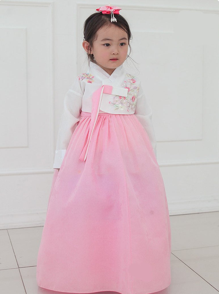 Young girl posing in a girls korean hanbok with white top and red skirt