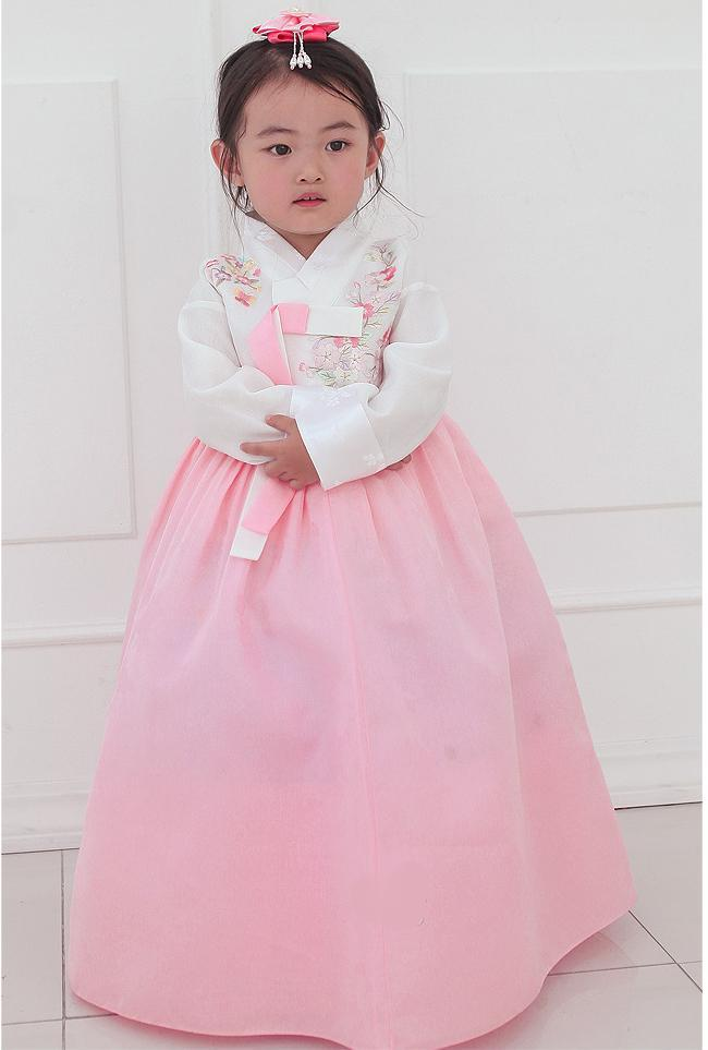 Young girl arms crossed while wearing a girls korean hanbok with white top and red skirt