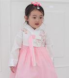 Young girl wearing a girls korean hanbok with white top and red skirt