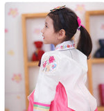 Young girl wearing headband and a girls korean hanbok with white top and red skirt