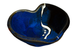 Cobalt blue and black bowl in the shape of a heart.  It's handmade pottery from Prairie Fire Pottery.  Hand made in stoneware clay.  3/4 view.