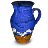 52 ounce wheel-thrown pitcher in cobalt blue and toasted brown.  Handmade pottery by Prairie Fire Pottery.  Hand made in stoneware clay and high-fired to 2400°.  Left side view.