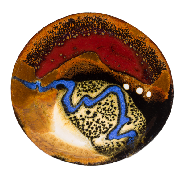 Small handmade pottery plate in earth tones and red, accented with a meandering ribbon of blue.  Hand made by Prairie Fire Pottery in stoneware clay.  Overhead view.