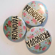 Load image into Gallery viewer, BRONCUDA Flower PIN BUTTON black font on blue and pink flowers 1.5""