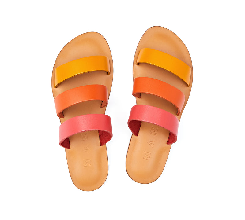 Top view of the handmade Sky women's slip-on leather sandals in natural tan insole with pomegranate, orange and yellow straps / SUNSET