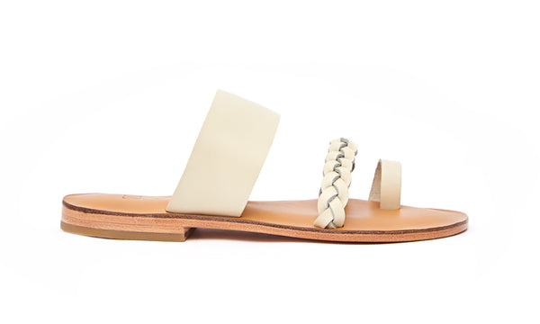 Side view of the handmade Sand women's braided slip-on leather sandals in natural tan insole with cream straps / CREAM