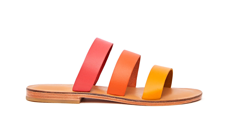Side view of the handmade Sky women's slip-on leather sandals in natural tan insole with pomegranate, orange and yellow straps / SUNSET