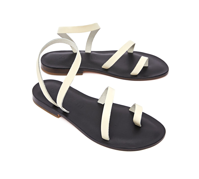 Angled view of the handmade Moon women's slingback leather sandals in black insole with cream straps / CREAM BLACK