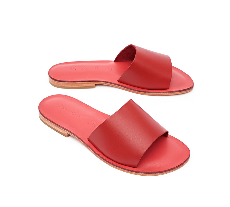 Angled view of the handmade Rock women's slip-on leather sandals in pomegranate insole with red straps / RED