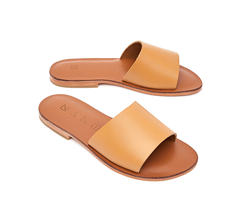 Angled view of the handmade Rock women's slip-on leather sandals in light brown insole with natural tan straps / TAN