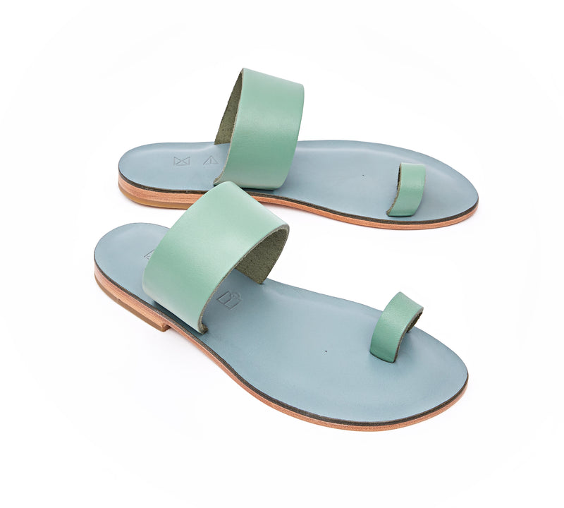 Angled view of the handmade Root women's slip-on leather sandals in light grey insole with light green straps / GREEN