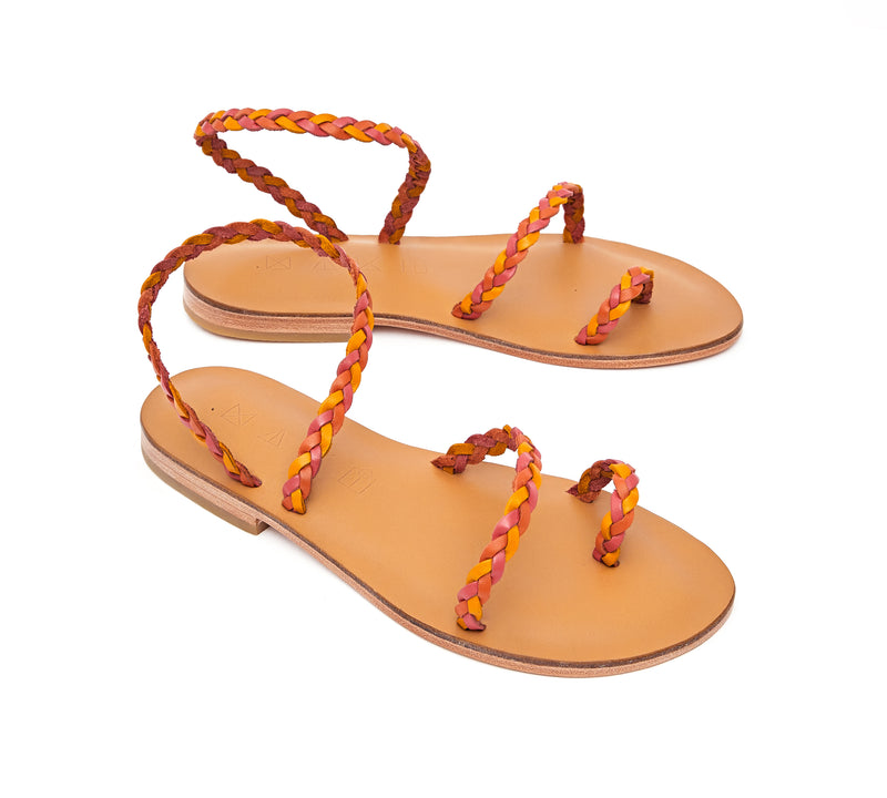 Angled view of the handmade Salt women's braided slingback leather sandals in natural tan insole with pomegranate, orange and yellow straps / SUNSET