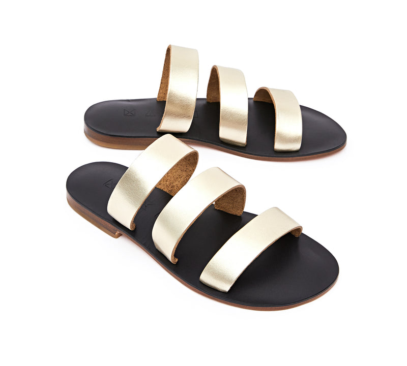 Angled view of the handmade Sky women's slip-on leather sandals in black insole with gold straps / GOLD BLACK