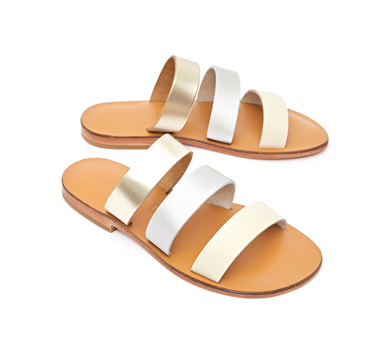 Angled view of the handmade Sky women's slip-on leather sandals in natural tan insole with gold, silver and cream straps / MOONLIGHT
