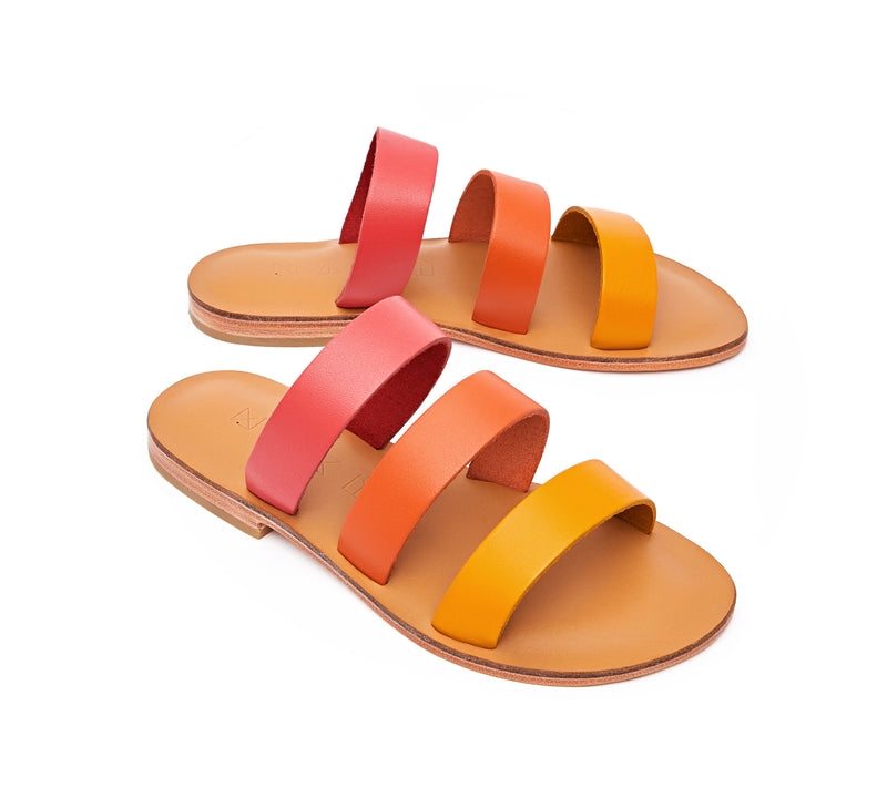 Angled view of the handmade Sky women's slip-on leather sandals in natural tan insole with pomegranate, orange and yellow straps / SUNSET