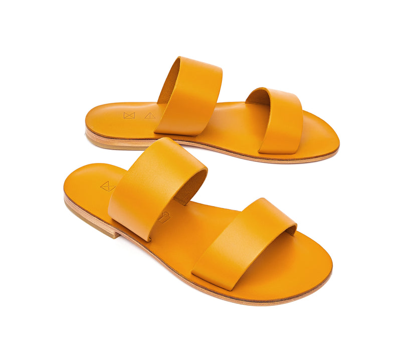 Angled view of the handmade Sun women's slip-on leather sandals in yellow / YELLOW