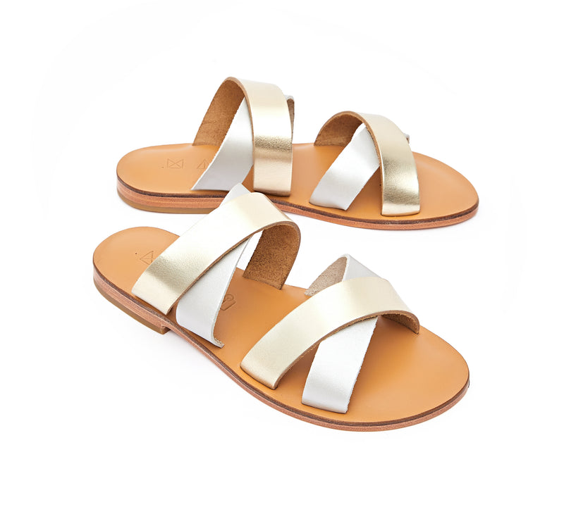 Angled view of the handmade Wave women's slip-on leather sandals in natural tan insole with gold and silver straps / GOLD SILVER
