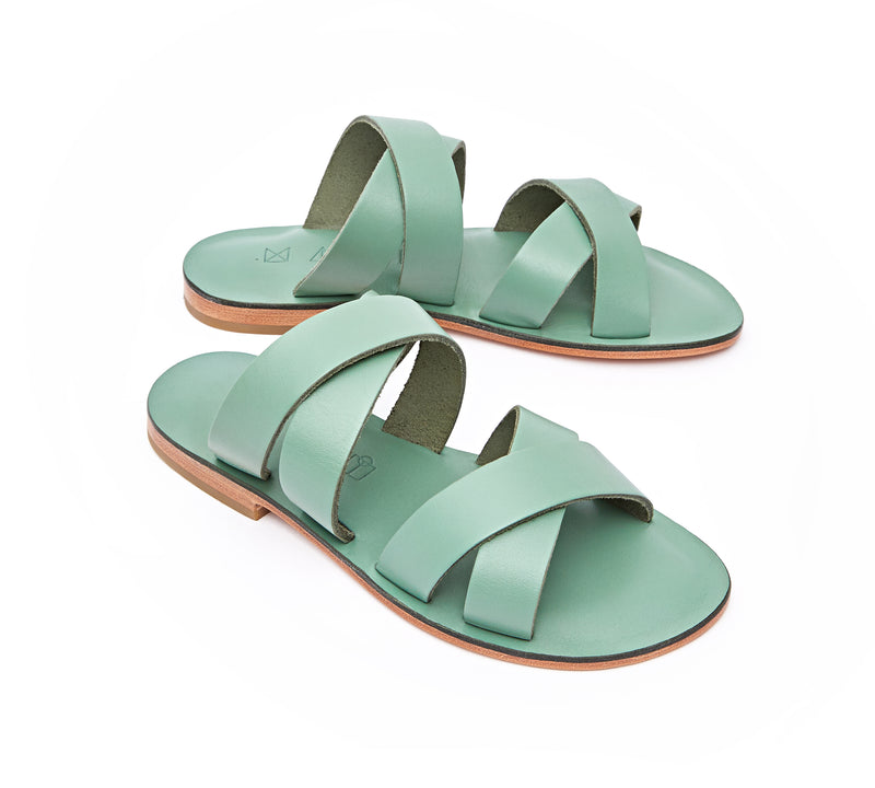 Angled view of the handmade Wave women's slip-on leather sandals in light green / GREEN