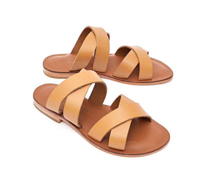 Angled view of the handmade Wave women's slip-on leather sandals in light brown insole with natural tan straps / TAN