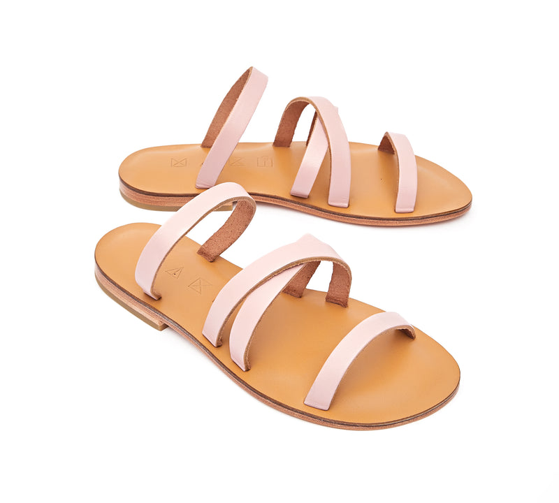 Angled view of the handmade Wind women's slip-on leather sandals in natural tan insole with light pink straps / PINK