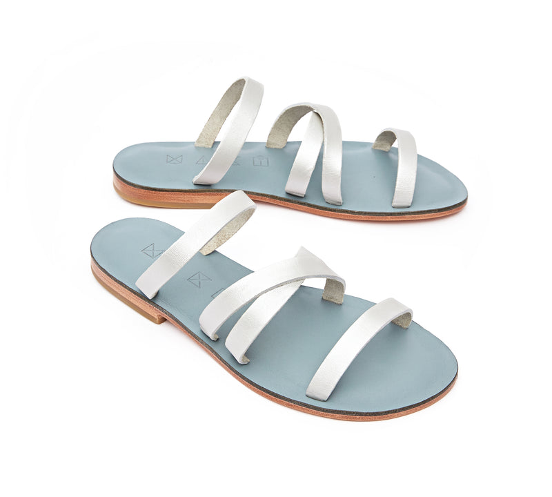 Angled view of the handmade Wind women's slip-on leather sandals in light grey insole with silver straps / SILVER