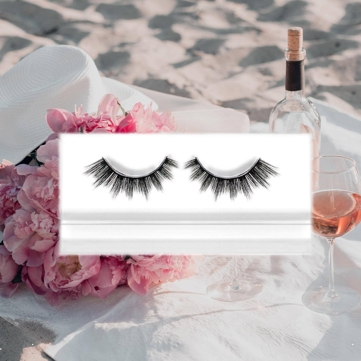 wispy styled volume base lashes with pink peonies beach champagne beach background