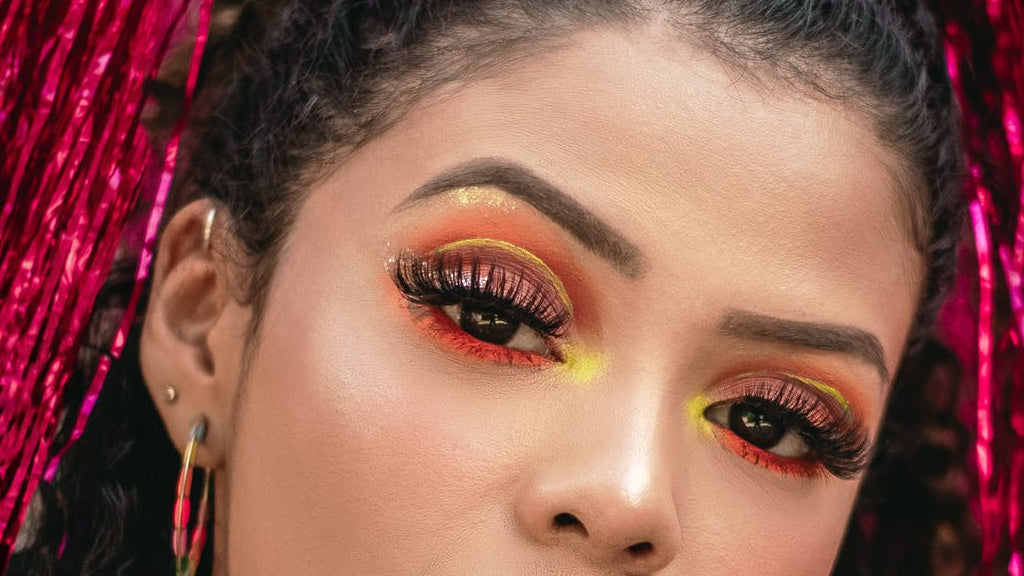 woman in colored necklace and colored earrings thick lashes